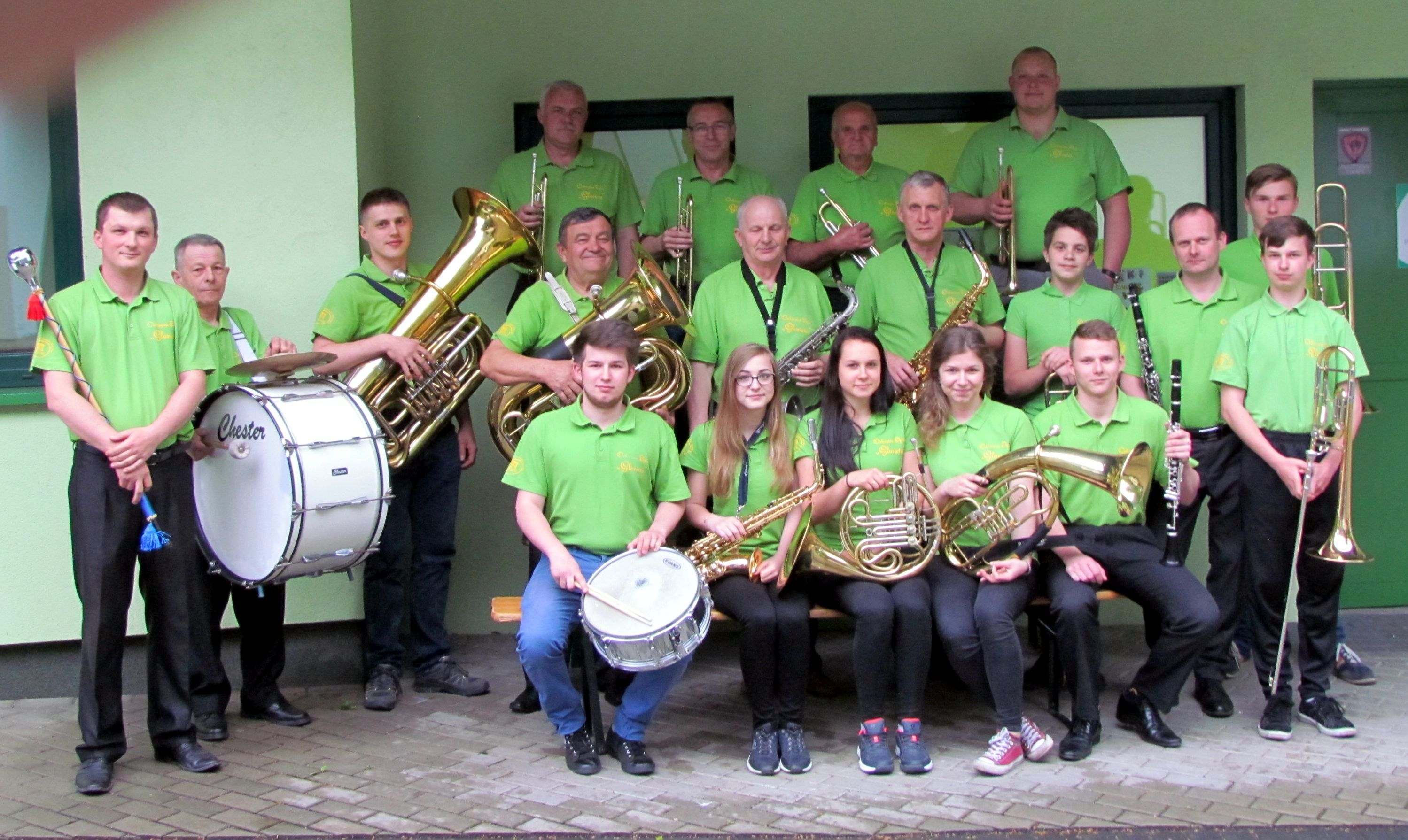 Muzycy Orkiestry Dętej Glorieta z instrumentami, stojący przed budynkiem biura Ośrodka Promocji Gminy Jaworze